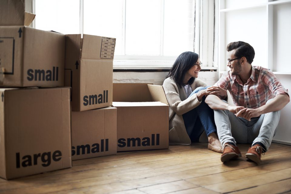 Couple in an apartment with packed moving boxes