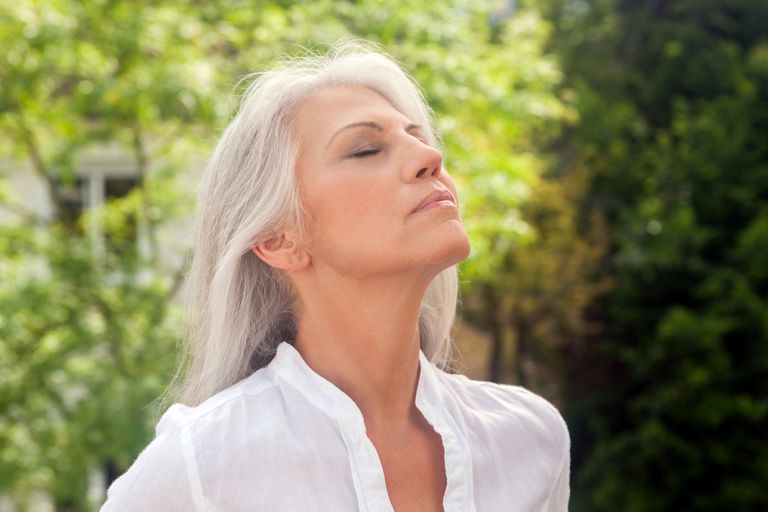 mature woman breathing deeply outdoors as a mindfulness practice