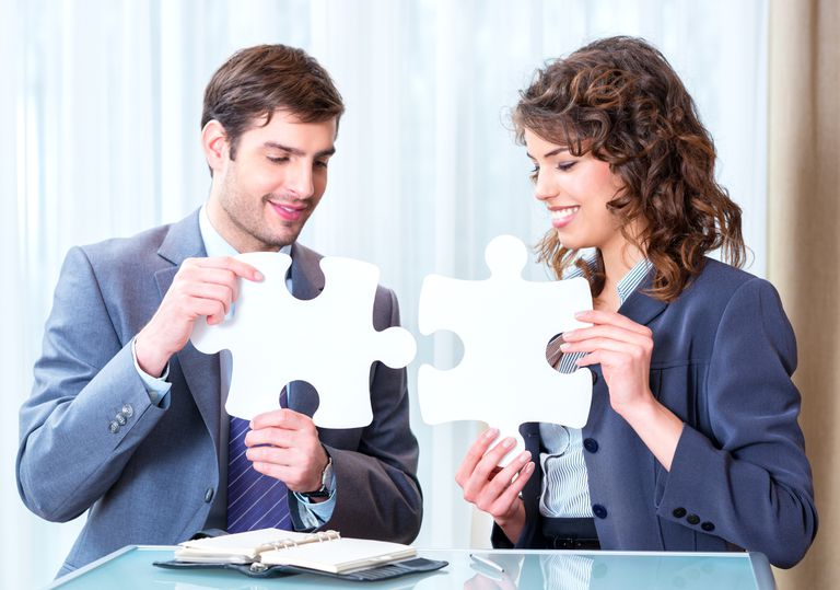 Man and woman coworkers fit puzzle pieces together. In an effective work relationship, pieces fit together