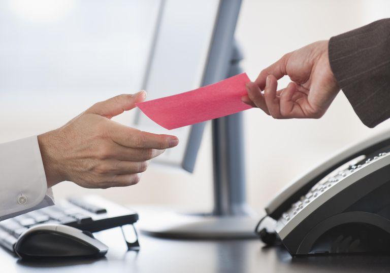 Business hand receiving a pink slip