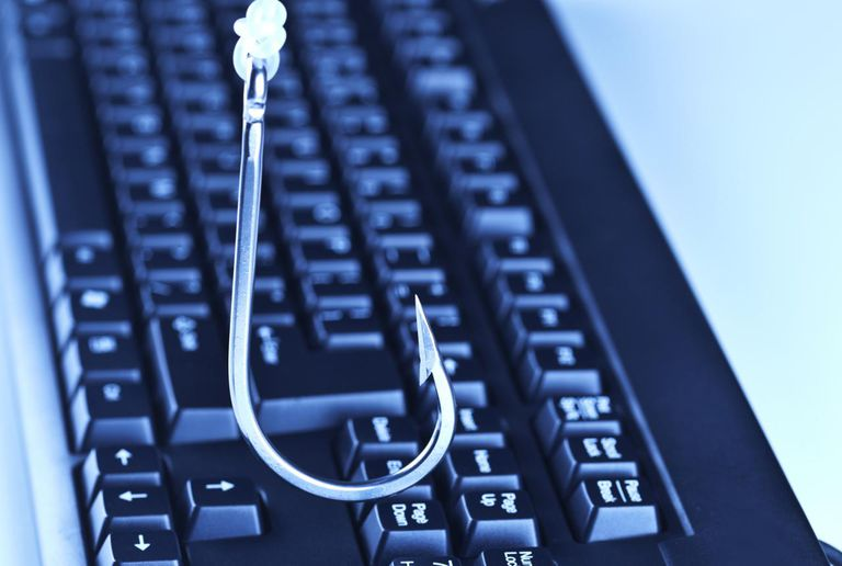 A hook dangles over a computer keyboard depicting computer fraud known as phishing