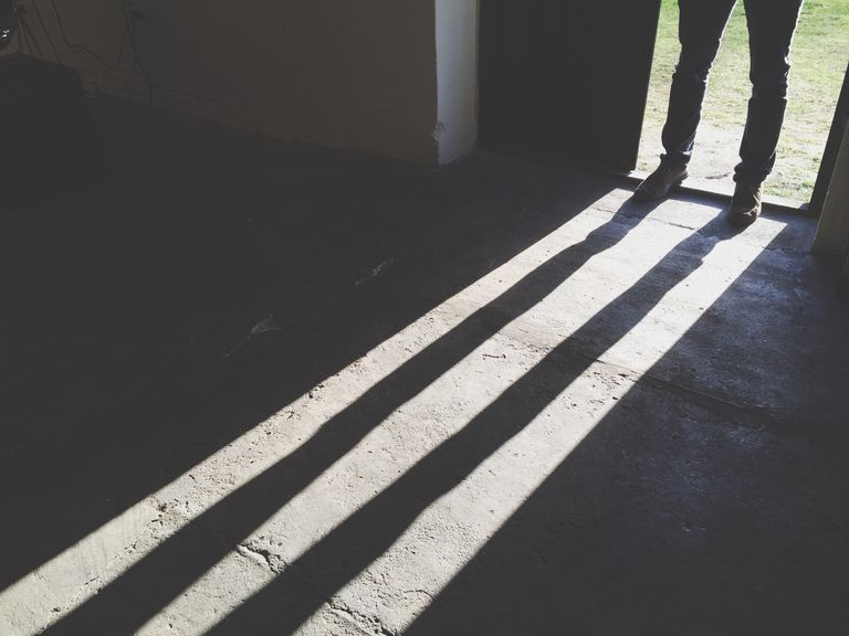 Low Section Of Man Standing On Doorway In Front Of Shadow At Home