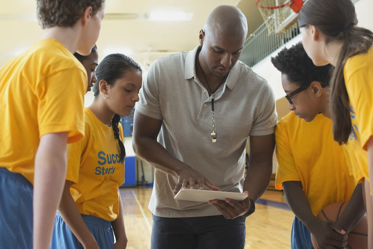 Coach using digital tablet with basketball team during practice in gym