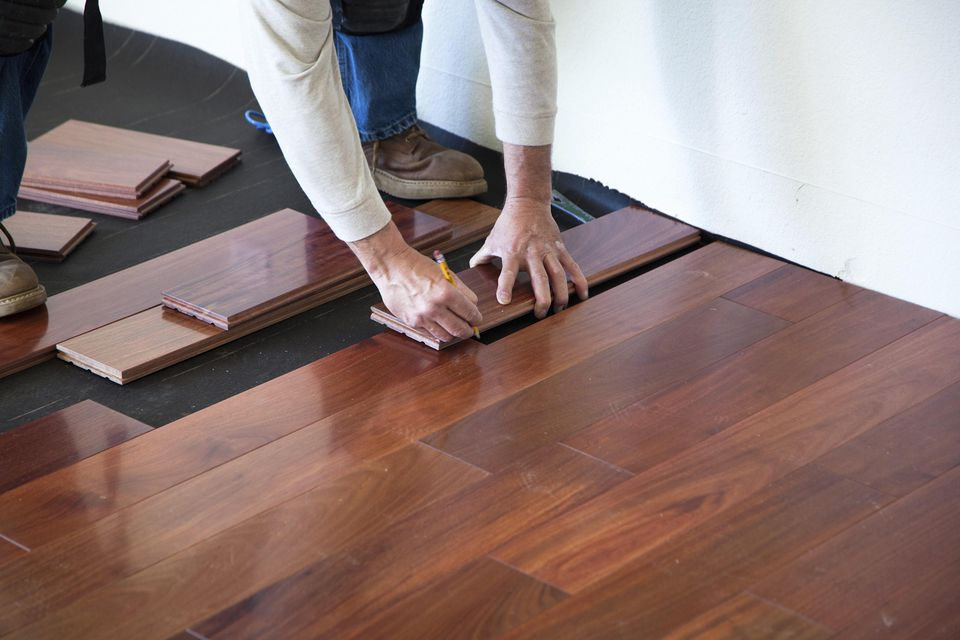 A worker installing hardwood floor in an American upscale home.A worker installing hardwood floor in an American upscale home.