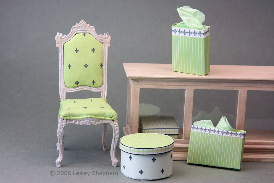 A newly upholstered dollhouse chair matches bags, boxes and other miniature shop fittings.