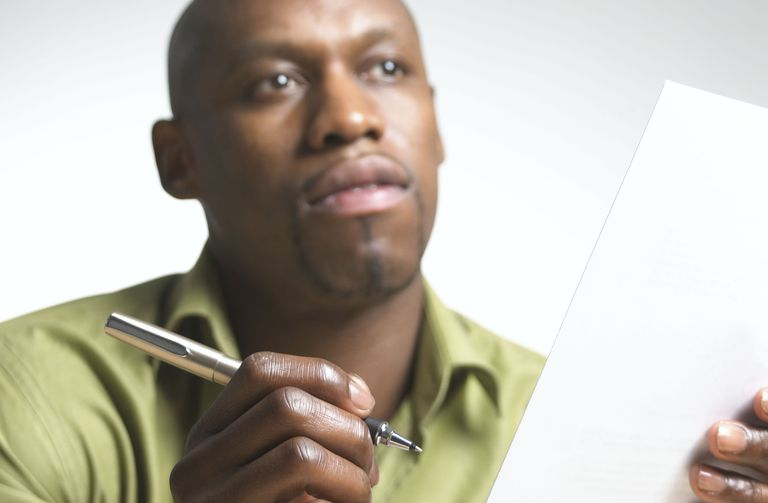 African-american man with pen thinking before signing a contract document