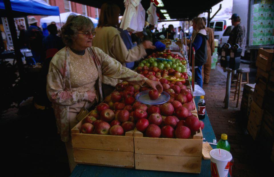 A shopper sampling an apple at the farmers' market at Eastern Market, Washington DC's main open-air market.