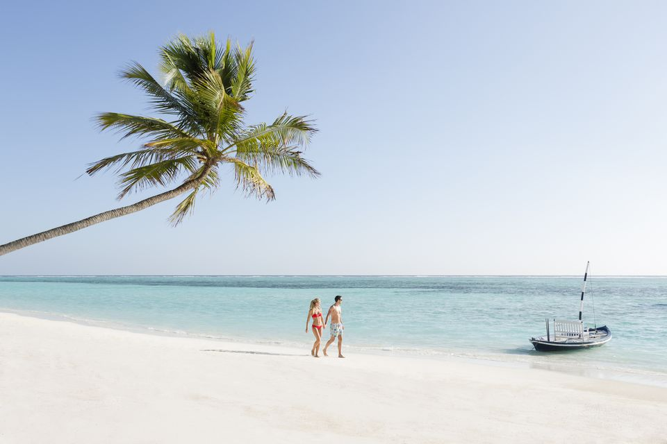 Couple walking on beach at island resort
