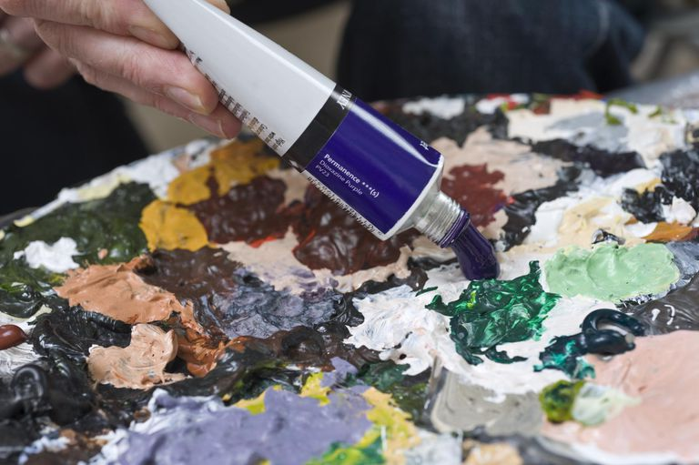 artist squeezing acrylic paint onto palette
