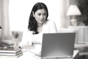 Mixed race woman studying on laptop