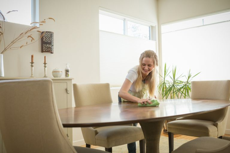 Woman cleaning dining room table
