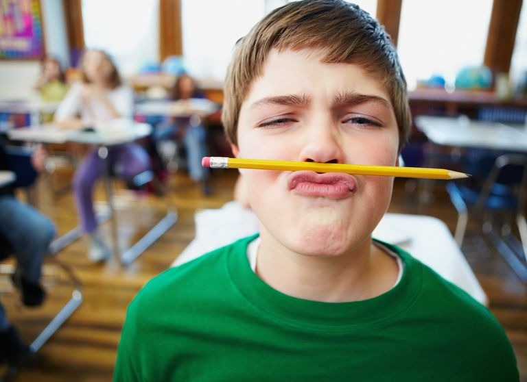 A boy playing with a pencil during class.
