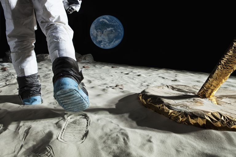 A man on the surface of the moon next to his shuttle