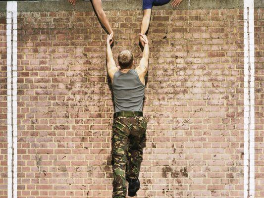 Men Helping a Man to Climb a Brick Wall on an Assault Course