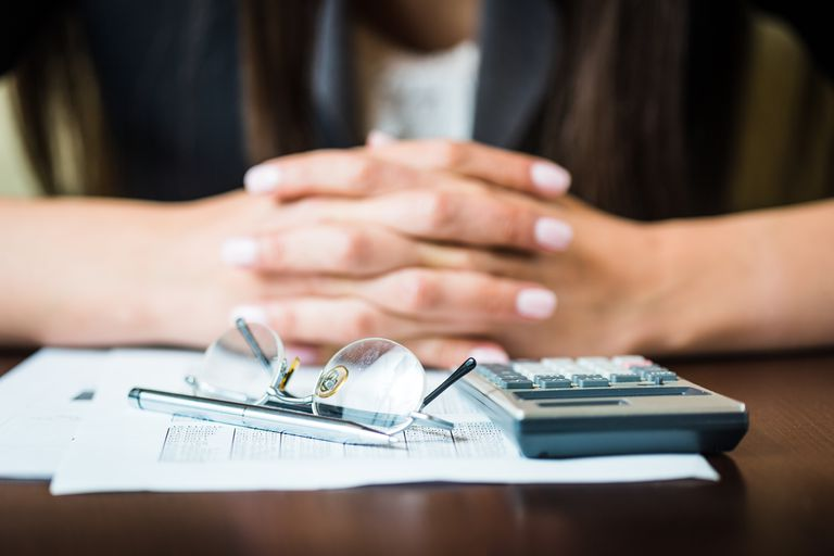 Close up of businesswoman's hands with pen, glasses, and calculator doing some financial calculations
