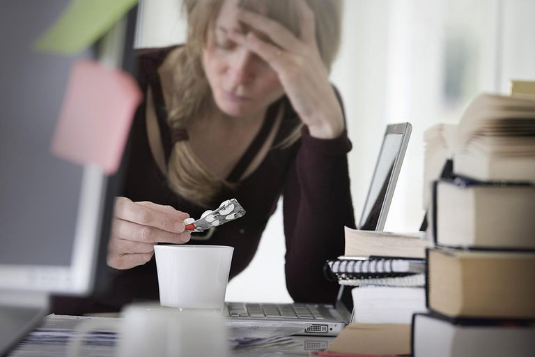 woman at her work station taking headache pills