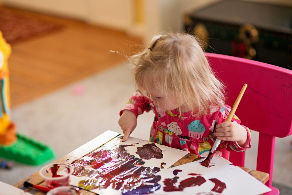 Toddler girl finger painting