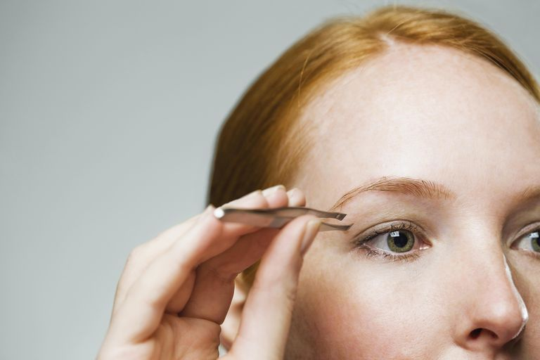 Close up of woman using tweezers on her eyebrow