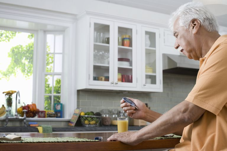 Man checking blood sugar in kitchen