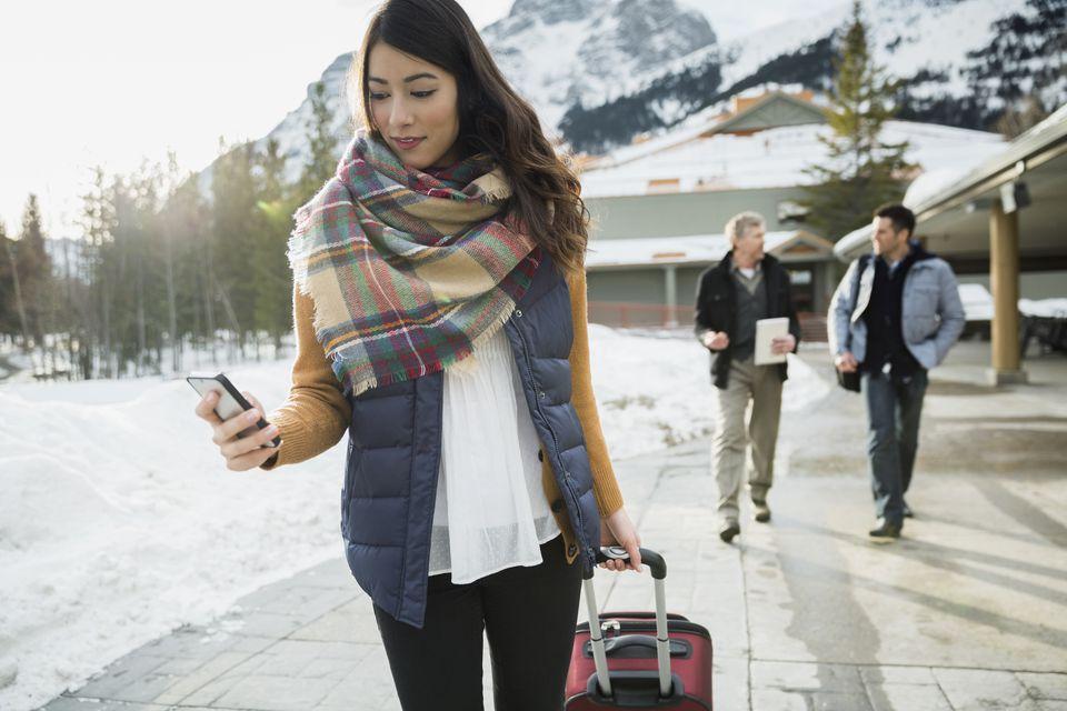 Woman pulling suitcase on sidewalk below mountains