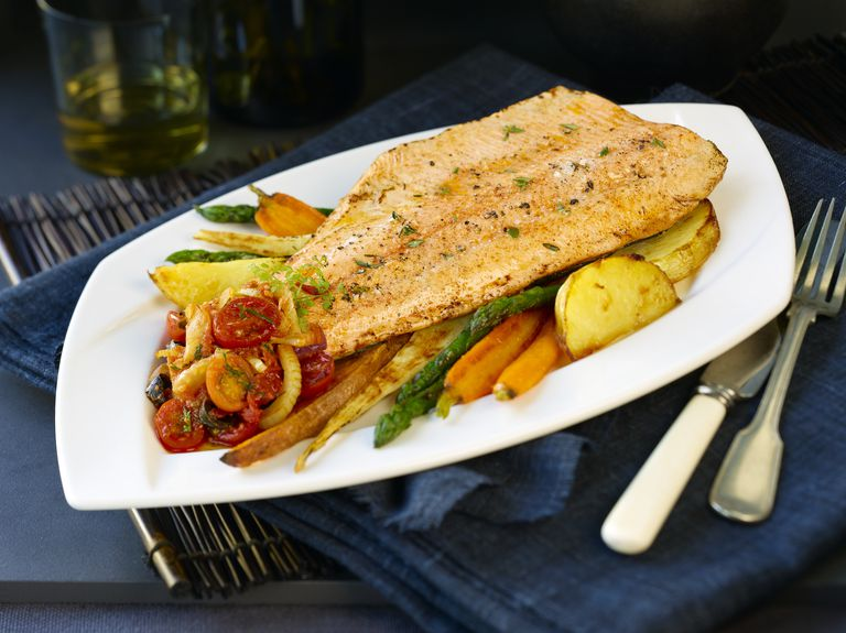 fish filet sitting on plate of roasted vegetables