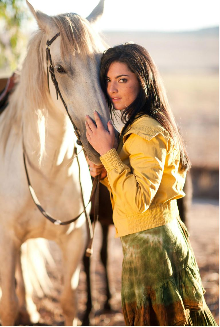 Young woman touching horse's face