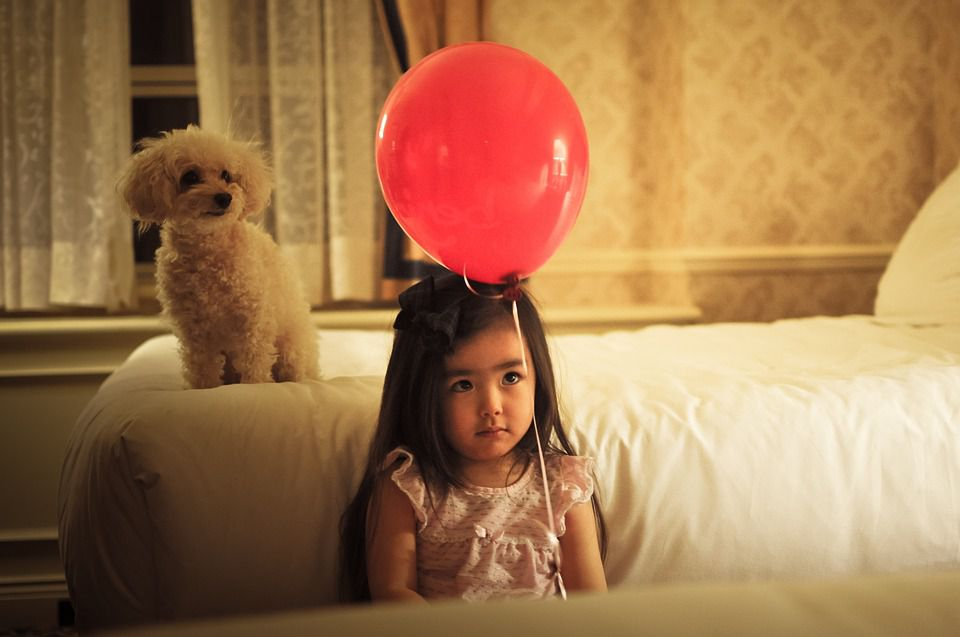 Girl with balloon and puppy.