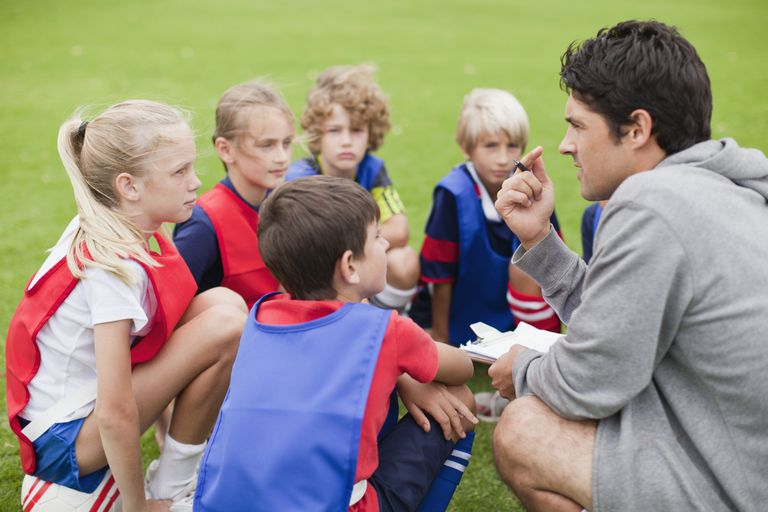 Coach talking with young players on field