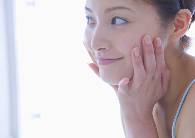 Woman admiring skin in mirror