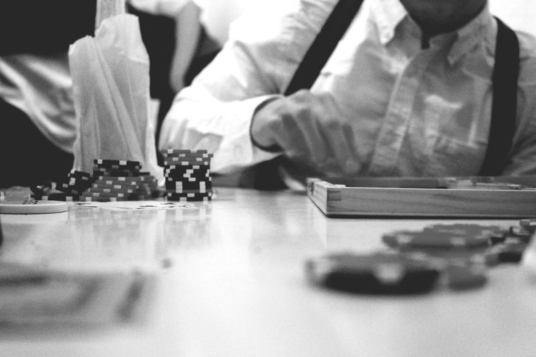 Man sitting at gaming table with stacks of poker chips