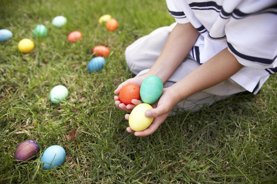Boy (6-7) holding Easter eggs in garden, close-up
