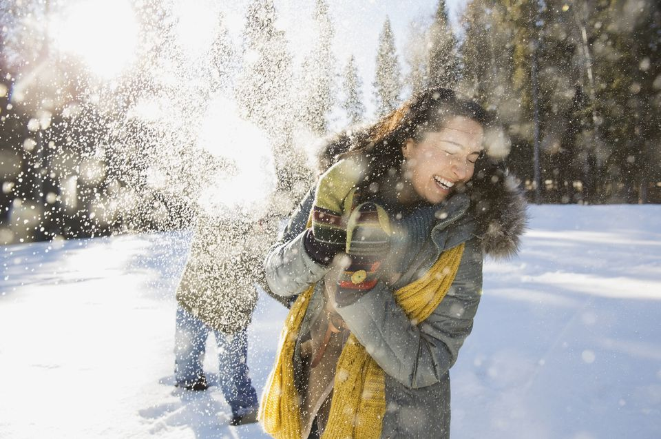 Couple in a snowball fight, warm clothing