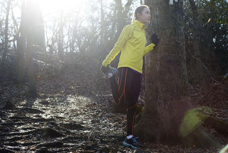 Woman stretching during run in a forest.