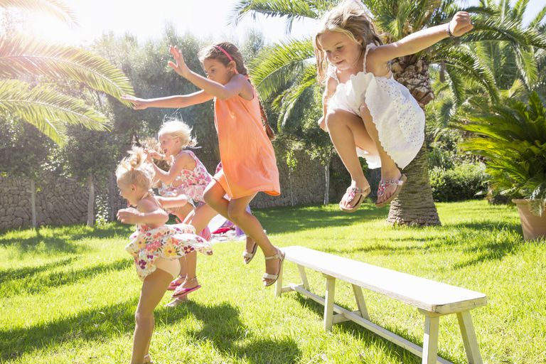 Active Little Girls Jumping Off a Bench