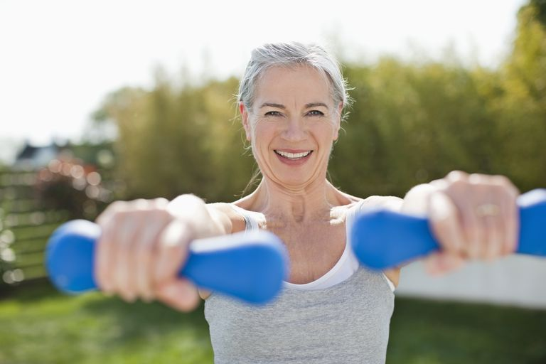 Older woman exercising with free weights outdoors