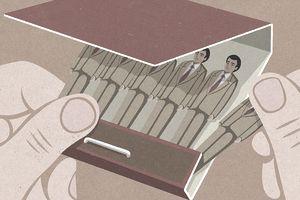 Hand removing businessman from matchbook (illustration)