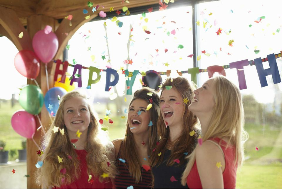Four teenage girls enjoying confetti at birthday party