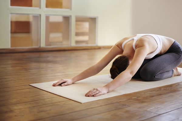Woman on a yoga mat in a studio doing child's pose