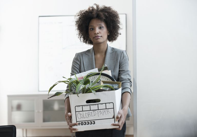 Businesswoman packing up box in office after her employment was terminated