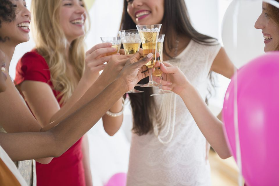 Women toasting each other with champagne at party
