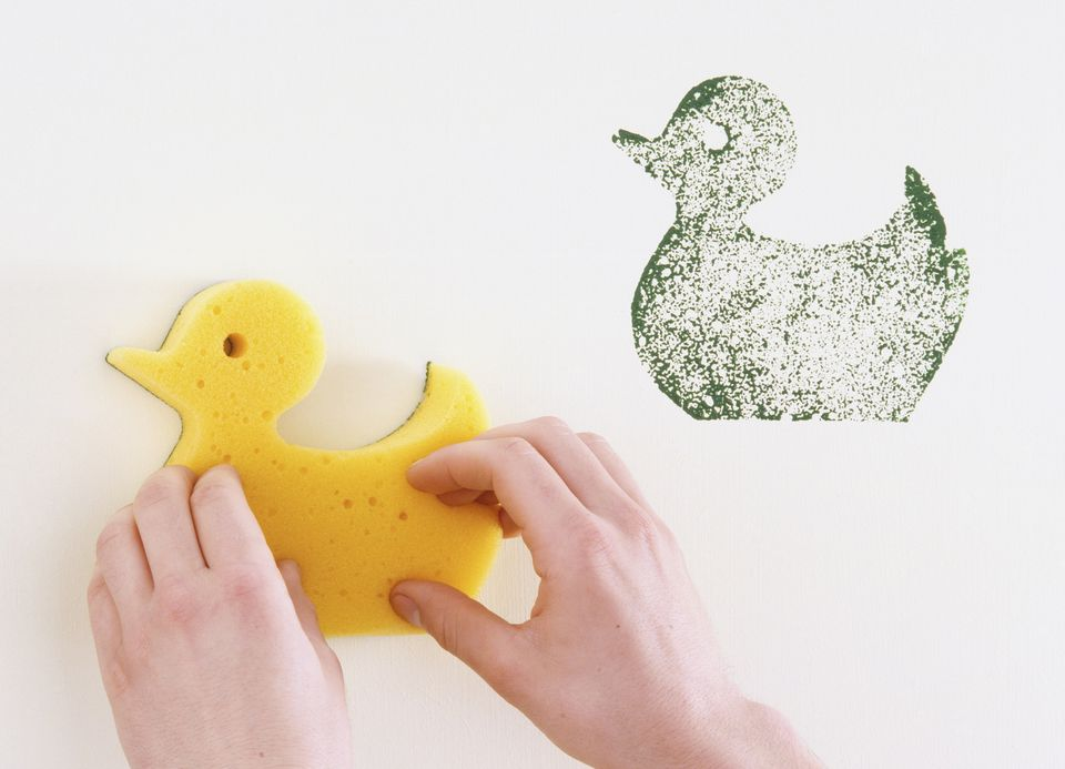 Using a duck shaped sponge to make green prints on a wall