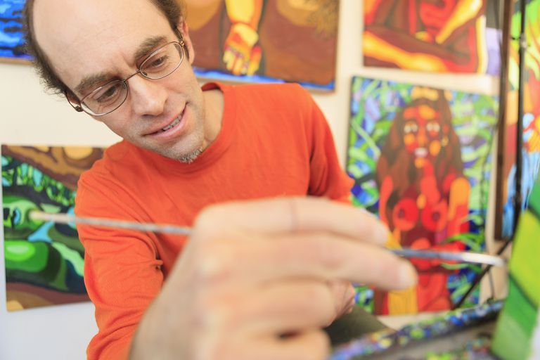 A man with Aspergers painting in his art studio