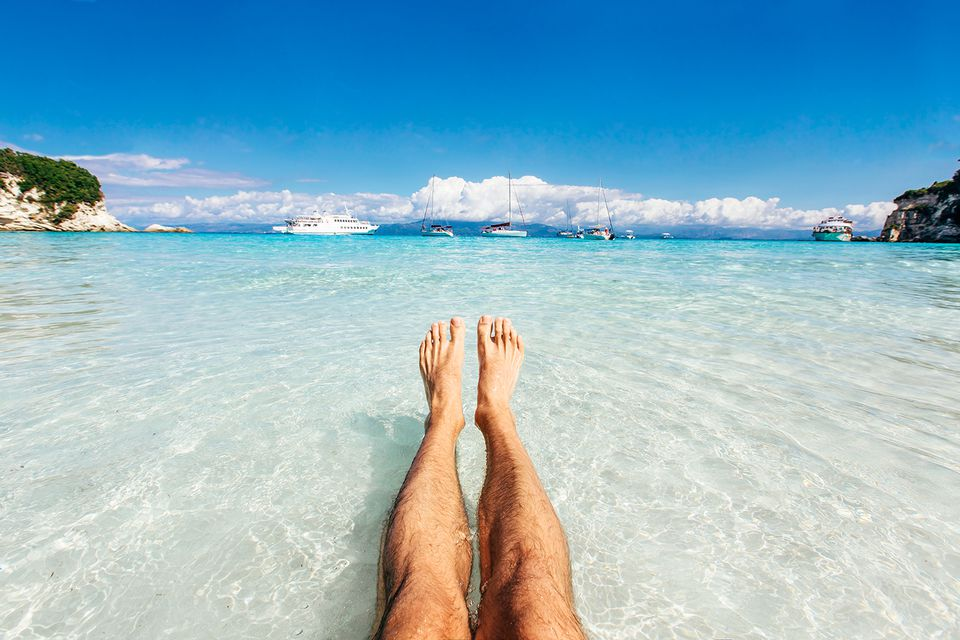 Personal perspective of man's feet in clear turquoise water