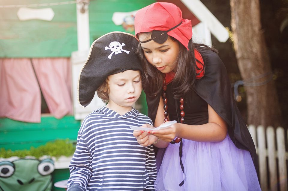 A pair of children dressed as pirates looking at clues