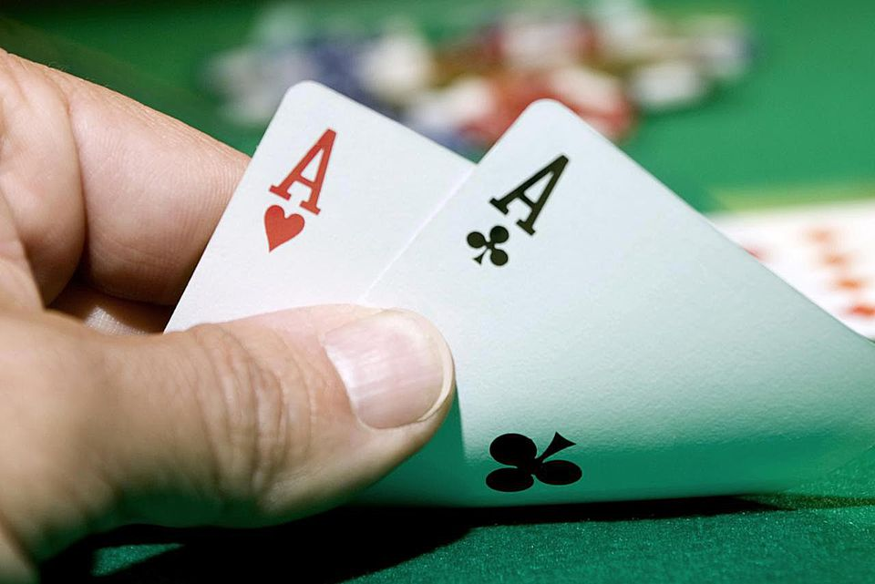 Man playing poker, close-up of hand and two aces