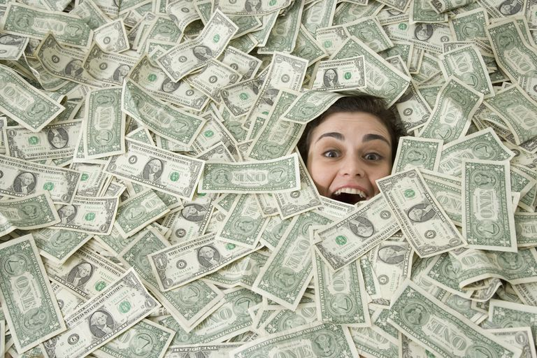 Woman's face peeking out of a pile of money