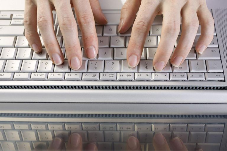 Fingers typing on laptop