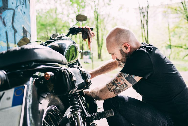 Mature male motorcyclist crouching to repair motorcycle