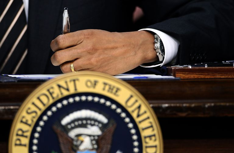 Close-up of President Obama's hand as he signs a bill