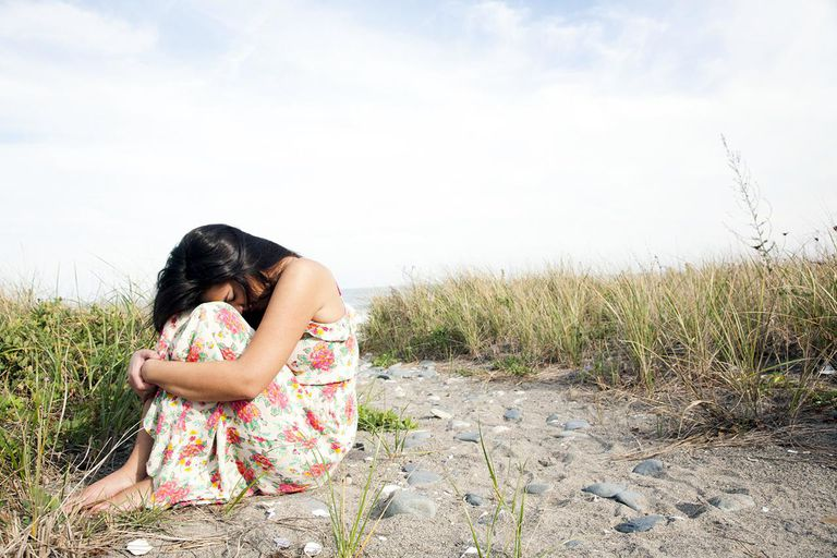 Woman hugging herself on beach